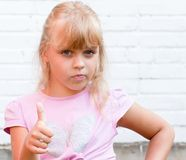Little blond beautiful girl with thumbs up. Portrait of a little blond beautiful Russian girl with thumbs up above white brick wall background Stock Photo