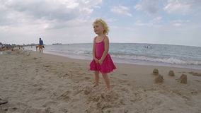 Little blond blue eyed baby girl playing on the beach video stock video