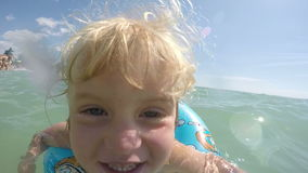 Little blond blue eyed baby girl playing in the water video stock footage