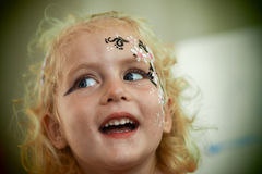 Little blond blue eyed girl face painting is smiling royalty free stock images