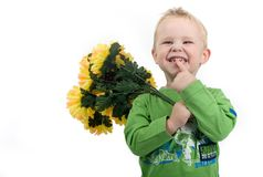 Little blond boy. With flowers in his hands smiling Royalty Free Stock Photography