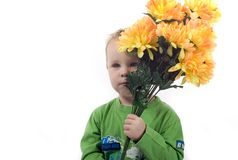 Little blond boy. With flowers in his hands smiling Royalty Free Stock Image