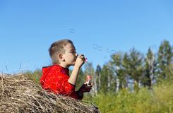 Little blond boy blow bubbles Stock Photo