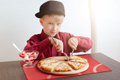 A little blond boy with blue eyes wearing red shirt and stylish cap sitting in cosy cafe eating delicious pizza and ice-cream look royalty free stock photos