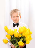 Little blond boy with bunch of flowers Royalty Free Stock Photography