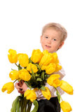 Little blond boy with bunch of flowers Royalty Free Stock Images
