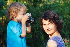 Little blond boy with a camera shoots her mother Stock Image