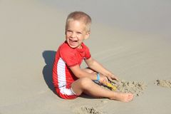 A little blond boy in clothes with UV filter is playing with sand on the beach by the sea, holiday with children, protecting kids. From the sun concept stock images