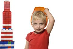Little blond boy in the construction helmet and a red shirt standing near the tower built from parts designer. Portrait. Isolate. On white background stock photography