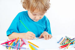 Little blond boy draws with color pencils Stock Photo
