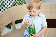 Little blond boy drinking healthy watermelon juice in summer. Royalty Free Stock Image