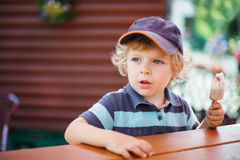 Little blond boy eating  ice cream in summer Royalty Free Stock Photography