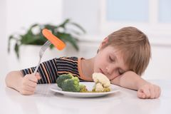 Little blond boy eating at kitchen. Royalty Free Stock Image