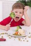Little blond boy eating at kitchen. Stock Images