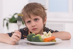 Little blond boy eating at kitchen. Stock Image