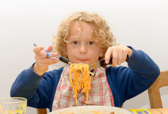Little blond boy eating pasta with tomato sauce royalty free stock image