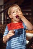 Little blond boy eating sweet cherries. Outdoor portrait Stock Image