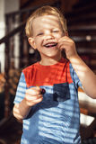 Little blond boy eating sweet cherries. Outdoor portrait Royalty Free Stock Photos