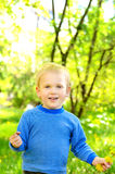 Little blond boy on green foliage background Royalty Free Stock Images