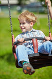Little blond boy having fun on swings Stock Photography