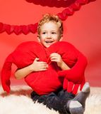 Little blond boy with heart pillow Stock Images