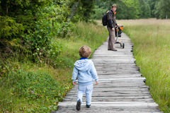 Little blond boy and his father walking through nature park Royalty Free Stock Images