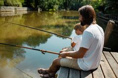 Little blond boy and his handsome father dressed in the white t-shirts are sitting with fishing rods on the wooden pier royalty free stock image