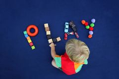Little blond boy with inscription PLAY made from different toys. On blue textile background. Childhood concept. Good for baby store stock photography