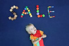Little blond boy with inscription SALE made from different toys. On blue textile background. Good for baby store royalty free stock image