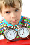 Little blond boy laid his head on two alarms Royalty Free Stock Photography