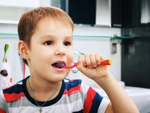 Little blond boy learning brushing his teeth in domestic bath. Kid learning how to stay healthy. Health care concept. Little blond boy learning brushing his Royalty Free Stock Photography