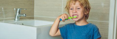 Little blond boy learning brushing his teeth in domestic bath. Kid learning how to stay healthy. Health care concept BANNER, long stock photos