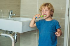 Little blond boy learning brushing his teeth in domestic bath. Kid learning how to stay healthy. Health care concept stock photo