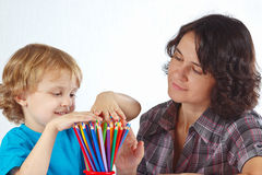 Little blond boy with mother looks on pencils Stock Photos