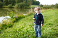 Little blond boy near forest lake, on summer evening Royalty Free Stock Photography