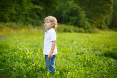 Little blond boy near forest lake, on summer evening Royalty Free Stock Photos