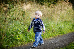 Little blond boy near forest lake, on summer evening Royalty Free Stock Image