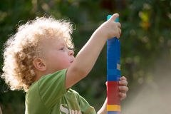 Little blond boy playing with blocks Stock Images