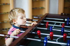 Little blond boy playing board table soccer at home. Stock Image