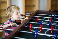 Little blond boy playing board table soccer at home. Royalty Free Stock Image