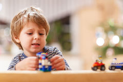Little blond boy playing with cars and toys at home, indoor. Stock Image