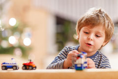 Little blond boy playing with cars royalty free stock photo