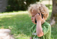 Little blond boy playing with a cell phone Royalty Free Stock Images