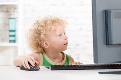 A little blond boy playing with  computer Royalty Free Stock Images