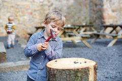 Little blond boy playing with hammer outdoors with brother. Stock Photos