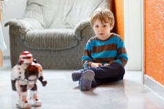 Little blond boy playing with robot toy at home, indoor. Royalty Free Stock Image