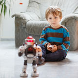 Little blond boy playing with robot toy at home, indoor. royalty free stock images
