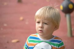 Little blond boy portrait in the park royalty free stock photo