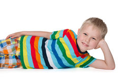 Little blond boy rests on the floor Stock Image