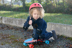 Little blond boy with  skateboard Stock Photos